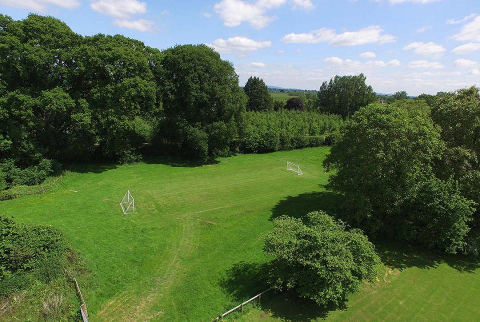 The huge playing field with football goals